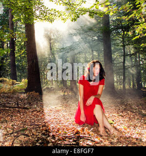 Woman sitting in forest in sunlight - Stock Photo