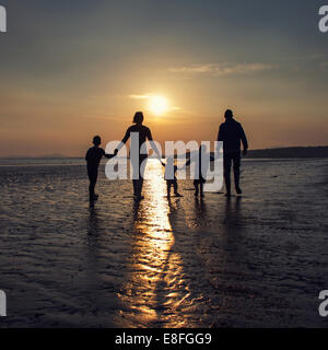 Silhouette of a Family on the beach holding hands - Stock Photo