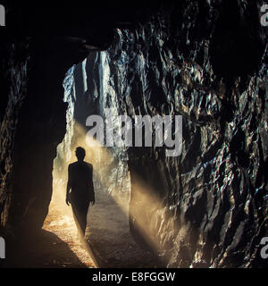 Silhouette of woman standing in sunlight in cave - Stock Photo