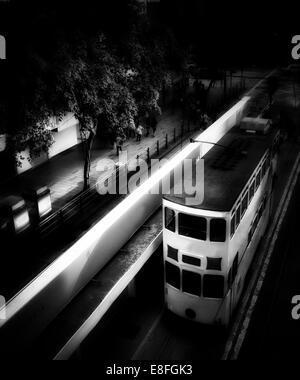 Tram driving through city at night, Hong Kong, China - Stock Photo