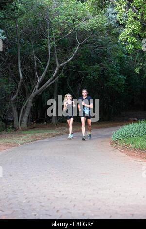 Couple jogging along footpath - Stock Photo