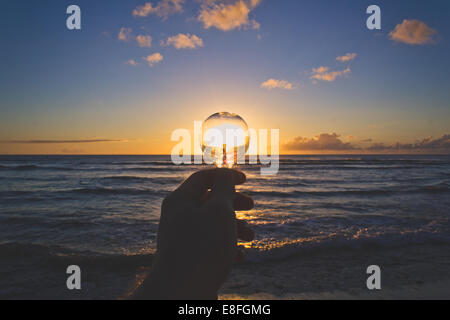 USA, Hawaii Islands, View of hand holding lightbulb at sunset - Stock Photo