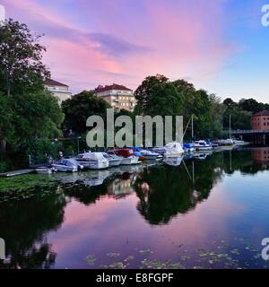 Sweden, Stockholm, Boats at jetty in summer at sunset - Stock Photo
