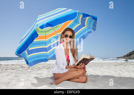 Woman reading a book on the beach sitting under a parasol - Stock Photo