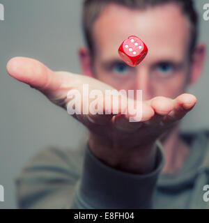 Man throwing dice in air - Stock Photo