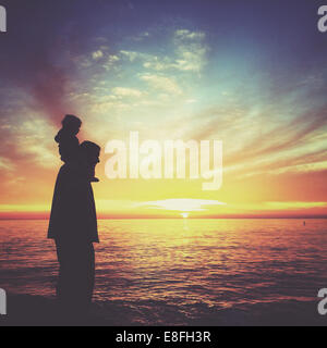 Silhouette of boy sitting on his father's shoulders, Laguna beach, California, America, USA - Stock Photo