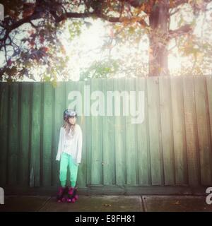 Girl wearing rollerskates leaning against fence - Stock Photo