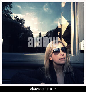 Portrait of a woman sitting in front of a window in the sun - Stock Photo