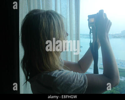 Woman taking photograph out of window - Stock Photo