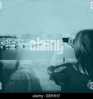 United Arab Emirates, Abu Dhabi, Woman taking photograph on phone - Stock Photo