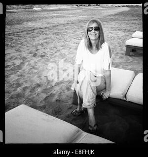 Smiling woman sitting on a sun lounger on beach, Muscat, Oman - Stock Photo