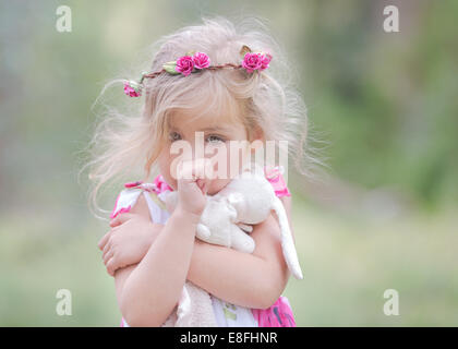 USA, Little girl (4-5) sucking thumb and clutching soft toy outdoors - Stock Photo