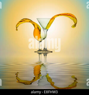 Yellow water splashing from two glasses standing side by side on water surface - Stock Photo