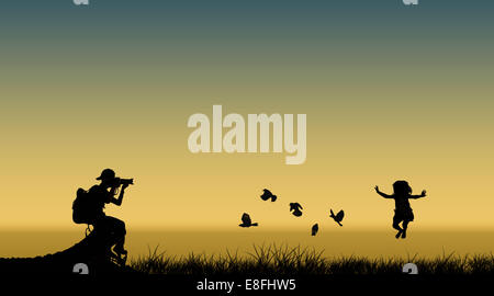 Silhouette of a photographer taking a photo of a girl jumping in air next to flying birds, Indonesia - Stock Photo