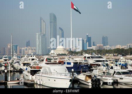 United Arab Emirates, Abu Dhabi, Skyline with harbor and boats in foreground - Stock Photo
