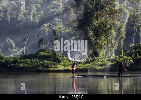 Indonesia, West Java, Karawang, Situ Gunung, Man throwing fishing net into water - Stock Photo