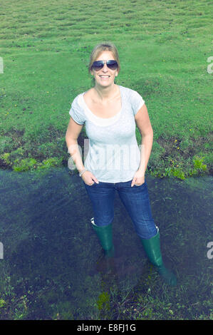 Portrait of a smiling woman standing in water, The New Forest, Hampshire, England, UK - Stock Photo