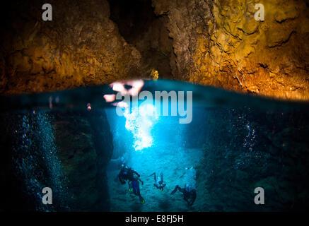 Four Scuba divers exploring Blue Cave, Okinawa, Japan - Stock Photo