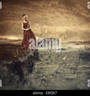 Girl looking out to sea - Stock Photo