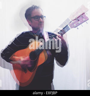 Portrait of man playing guitar - Stock Photo