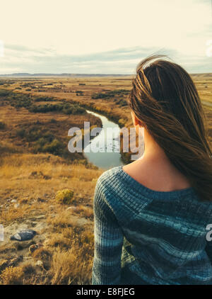 Canada, Saskatchewan, Val Marie, Rear view of woman overlooking prairie and river vista in fall - Stock Photo