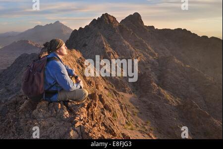 USA, Arizona, Portrait of man meditating on top of Mohawk Mountains - Stock Photo