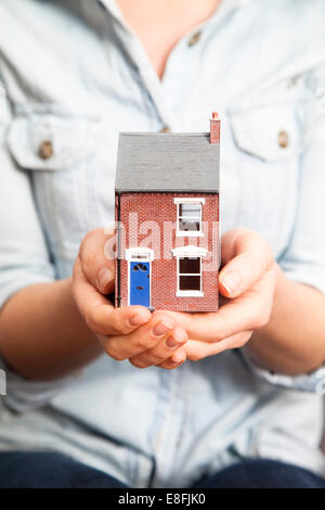 Woman's hands holding model house - Stock Photo