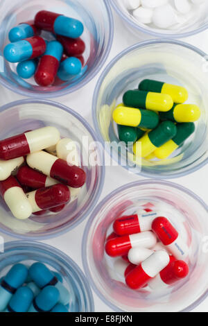 Glass bowls with multi-colored pills - Stock Photo