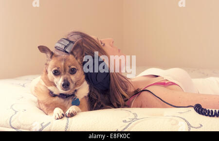 Young woman lying on bed with dog - Stock Photo