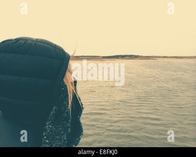 Close-up of a woman standing on a boat with a hood covering her face, Fanoe, Jutland, Denmark - Stock Photo