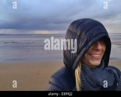 Somerset, UK Smiling Woman At Beach During Stormy Weather - Stock Photo