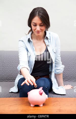 Woman putting coin into piggy bank - Stock Photo