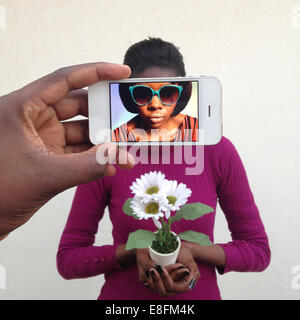 Man photographing a young woman using a mobile phone and seeing her alter ego on the screen
