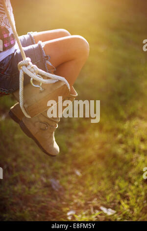 Close-up of a girl's legs sitting on a rope swing in the garden, Mississippi, USA - Stock Photo