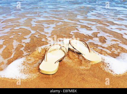 Flip flops on beach in surf - Stock Photo