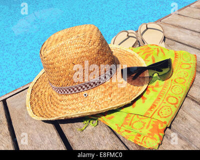 Straw hat, sunglasses, flip flops and sarong on wooden deck by swimming pool - Stock Photo