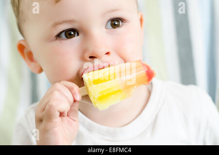 Baby boy eating ice lolly - Stock Photo