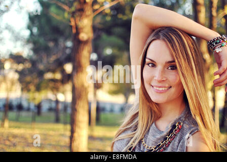 Portrait of smiling young woman standing in a park - Stock Photo