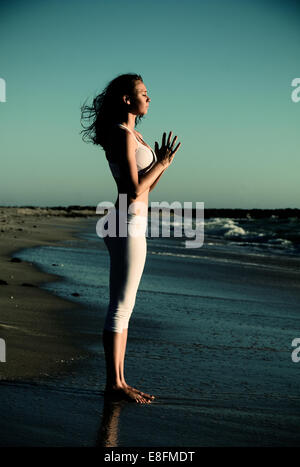 Side view of woman standing on beach doing yoga with hands in prayer position - Stock Photo