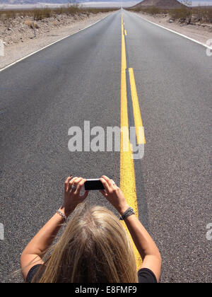 Woman taking photo of infinity road with mobile phone, Nevada, America, USA - Stock Photo