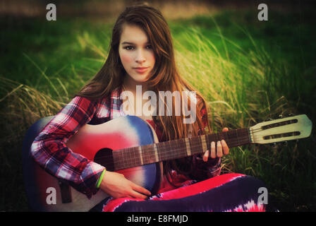 Portrait of a teenage girl sitting in a meadow with her guitar, Poland