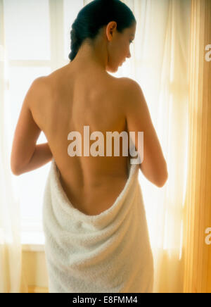 Rear view of woman Woman wrapped in towel - Stock Photo