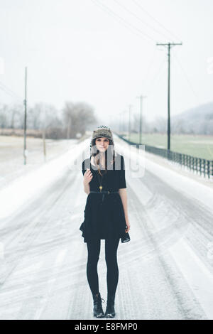 Young woman standing in the road in winter - Stock Photo