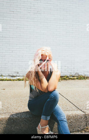 USA, Tennessee, Davidson County, Nashville, Young woman sitting on curb - Stock Photo