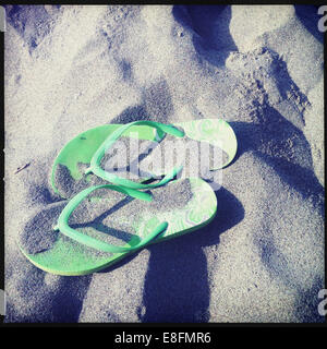 Overhead view of pair of Green flip-flops on sand - Stock Photo