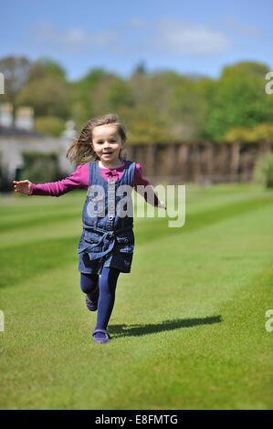 Little girl (4-5) running on green grass - Stock Photo