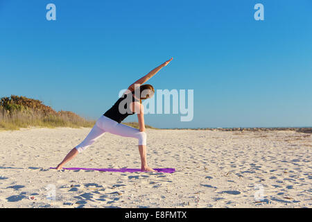 Rear view of woman doing yoga on beach - Stock Photo