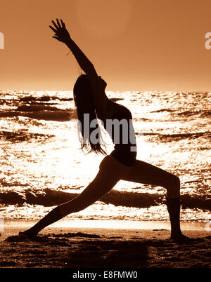 Silhouette of Woman practicing warrior 1 yoga pose on beach - Stock Photo