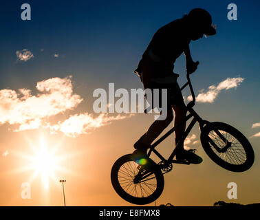 Silhouette of boy doing stunts on his bmx bike - Stock Photo