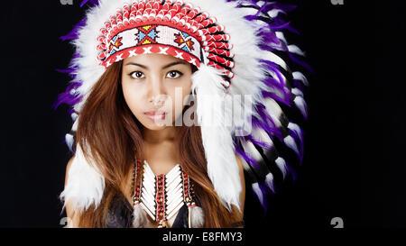 Studio portrait of woman wearing Native American headdress